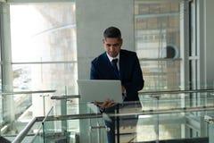 Het vooraanzicht van zakenman leunde op het traliewerk en het werken aan zijn laptop in het bureau van de fisrtvloer royalty-vrije stock fotografie
