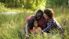 Het voorbeeldige paar wijdt hun vrije tijd aan slechts kind, die in de zomerpark ontspannen royalty-vrije stock foto's