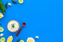 Het voorbereiden van de Griekse saus van de komkommeryoghurt Kom met yoghurt dichtbij groen, komkommer, sinaasappelen, knoflook o Stock Afbeelding