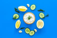 Het voorbereiden van de Griekse saus van de komkommeryoghurt Kom met yoghurt dichtbij groen, komkommer, sinaasappelen, knoflook o Royalty-vrije Stock Foto