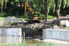 Het voorbereiden van de plaats voor insluitingsvijver Park bosachtergrond Mannelijke arbeiders in het water stock foto