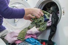 Het voorbereiden van de wascyclus Wasmachine, handen en kleren royalty-vrije stock fotografie