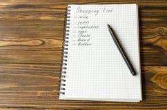 Het voorbereiden van de het winkelen lijst alvorens de kruidenierswinkels te gaan kopen royalty-vrije stock afbeelding