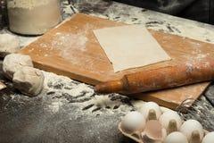 Het voorbereiden van een gerold deeg op houten raad stock foto's