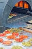 Het voorbereiden van een smakelijke pizza in de oven Stock Foto's