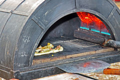 Het voorbereiden van een smakelijke pizza in de oven Stock Afbeelding