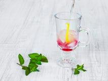 Het voorbereiden van een verfrissende cocktail van mineraalwater, citroen, framboos, munt en ijs stock afbeeldingen