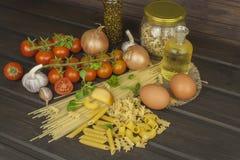Het voorbereiden van eigengemaakte deegwaren Deegwaren en groenten op een houten lijst dieet voedsel Stock Foto