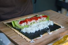 Het voorbereiden van eigengemaakte sushi met witte rijst, tonijn, tomaten en salade op een droog blad van het norizeewier op bamb royalty-vrije stock foto