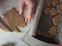Het voorbereiden van gemberkoekjes verwijdert het oude mes in de vorm van een hart en Kerstboomkoekjes stock afbeelding