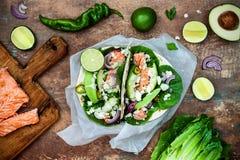 Het voorbereiden van gezonde lunchsnacks Vissentaco's met geroosterde zalm, rode ui, de verse saladebladeren en saus van de avoca stock fotografie