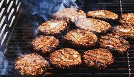 Het voorbereiden van heerlijke hamburgers op de openluchtgrill voor familie l royalty-vrije stock afbeeldingen
