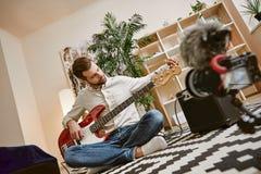 Het voorbereiden van instrument Knappe mannelijke muziek blogger het aanpassen elektrische gitaar voor het registreren van nieuwe royalty-vrije stock foto's