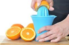 Het voorbereiden van 100% jus d'orange Stock Fotografie