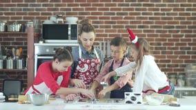 Het voorbereiden van Kerstmiskoekjes Moeder en drie kinderen in de keuken stock video