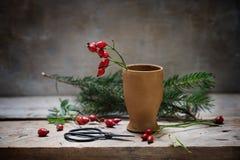 Het voorbereiden van natuurlijke Kerstmisdecoratie met rozebottels in een steen stock foto