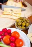 Het voorbereiden van olijven en Emmenthal kaas Stock Afbeeldingen