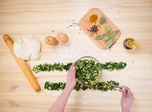 Het voorbereiden van pastei met spinazie en feta-kaas, voedsel cooking Hoogste mening stock foto