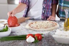 Het voorbereiden van pizza met salami Stock Foto