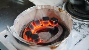 Het voorbereiden van sintels voor een waterpijp burning stock videobeelden