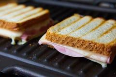 Het voorbereiden van smakelijke toost met ham en kaas royalty-vrije stock afbeeldingen