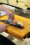 Het voorbereiden van vissen aan kok Stock Fotografie