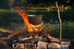 Het voorbereiden van voedsel in grote pot op kampvuur Stock Afbeeldingen