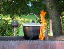 Het voorbereiden van voedsel op kampvuur Stock Fotografie