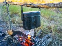 Het voorbereiden van voedsel op kampvuur in het wilde kamperen Stock Afbeeldingen