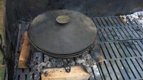 Het voorbereiden van voedsel in pot op net Rookstijging van steenkool Handbediend schot stock videobeelden