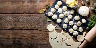 Het voorbereidingen treffen, koken, die eigengemaakte ravioli, pelmeni of bollen met vlees op de houten mening van de lijstbovenk Stock Afbeelding