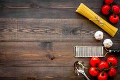 Het voorbereidingen treffen om deegwaren te koken Spaghetti, tomaten, knoflook, kaasrasp, lepel voor spaghetti op de donkere hout Stock Afbeelding