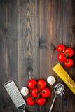 Het voorbereidingen treffen om deegwaren te koken Spaghetti, tomaten, knoflook, kaasrasp, lepel voor spaghetti op de donkere hout Royalty-vrije Stock Afbeeldingen