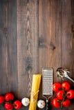 Het voorbereidingen treffen om deegwaren te koken Spaghetti, tomaten, knoflook, kaasrasp, lepel voor spaghetti op de donkere hout Stock Fotografie