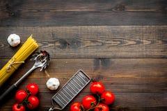 Het voorbereidingen treffen om deegwaren te koken Spaghetti, tomaten, knoflook, kaasrasp, lepel voor spaghetti op de donkere hout Royalty-vrije Stock Afbeelding