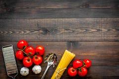 Het voorbereidingen treffen om deegwaren te koken Spaghetti, tomaten, knoflook, kaasrasp, lepel voor spaghetti op de donkere hout Stock Foto