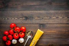 Het voorbereidingen treffen om deegwaren te koken Spaghetti, tomaten, knoflook, kaasrasp, lepel voor spaghetti op de donkere hout Stock Foto's