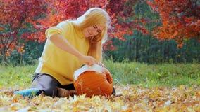 Het voorbereidingen treffen voor de de herfstvakantie en Hellouvinu Een vrouw past beeld op de grote pompoen toe stock footage