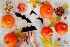 Het voorbereidingen treffen voor Halloween De knuppels van de handenbesnoeiing uit document Cijfers en pompoenen op grijze hoogst Royalty-vrije Stock Foto's