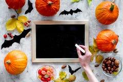 Het voorbereidingen treffen voor Halloween Zwart bureau voor nota's onder pompoenen en knuppels op grijs achtergrond hoogste meni Stock Afbeeldingen