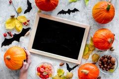 Het voorbereidingen treffen voor Halloween Zwart bureau voor nota's onder pompoenen en knuppels op grijs achtergrond hoogste meni Royalty-vrije Stock Afbeeldingen