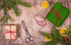 Het voorbereidingen treffen voor Kerstmis Verpakking van giften Nette takken, oranje, gebreide gift en messen Oma` s gift Royalty-vrije Stock Afbeelding