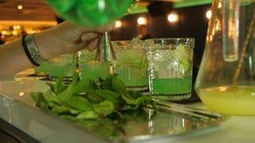 Het voorbereidingsproces van cocktails, de barman met een metende kop voor barmannen meet de dosis mineraal stock footage