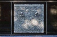 Het voordeel van de granietcrypt met de handvatten van de metaalring in cemeter Stock Afbeelding