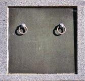 Het voordeel van de granietcrypt met de handvatten van de metaalring in cemeter Royalty-vrije Stock Afbeelding