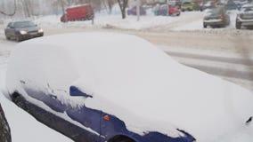 Het voordiedeel van een auto in sneeuw na een blizzard wordt begraven stock footage