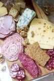 Het voorgerecht van diverse types van worsten, vlees, kazen en crackers op een houten raad, diende aan wijn royalty-vrije stock foto