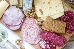 Het voorgerecht van diverse types van worsten, vlees, kazen en crackers op een houten raad, diende aan wijn stock afbeelding