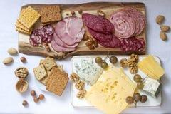 Het voorgerecht van diverse types van worsten, vlees, kazen en crackers op een houten raad, diende aan wijn royalty-vrije stock foto's