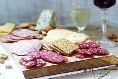 Het voorgerecht van diverse types van worsten, vlees, kazen en crackers op een houten raad, diende aan wijn stock fotografie
